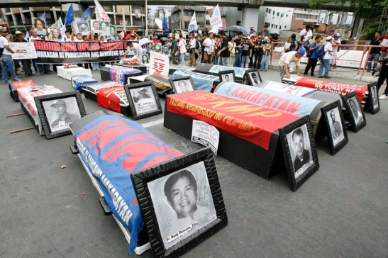 Protesters display black coffins during a protest outside the presidential palace in Manila