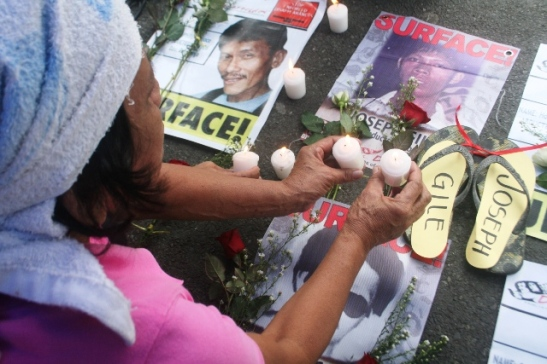 An elderly Filipino woman lighting candles for victims of enforced disappearances in the Philippines (photo courtesy of Bulatlat).