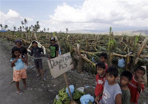 Residents affected by typhoon Pablo beg for aid from passing motorists in Montevista township, Compostela Valley (photo by Bullit Marquez/AP).