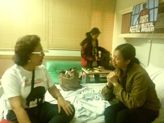 Ericson Acosta, left, at his hospital bed talking to supporter and fellow artist Bibeth Orteza (photo by Sarah Raymundo).