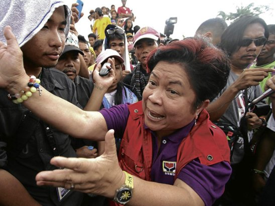 """Social Welfare Secretary Corazon Soliman tries to talk to residents occupying a highway in Compostela Valley to protest what they said was the uneven distribution of relief goods to survivors of Typhoon """"Pablo"""" (photo by Karlos Manlupig/Inquirer News)."""