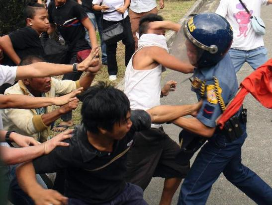 Cops breaking up protesting farmers and peasants outside of the Department of Agriculture, where the National Anti-Poverty Commission office is located (photo courtesy of Reuters).