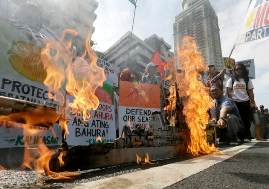 Protesters set on fire to a mock model of the USS Guardian, a US Navy minesweeper which ran aground off Tubbataha Reef in southwestern Philippines, during a rally to demand the pull out of US troops in the country (photo by photo by Bullit Marquez/AP Photo).