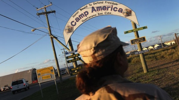 "A U.S. Navy sailor passes by a sign at the U.S. detention center for ""enemy combatants"" on September 16, 2010 in Guantanamo Bay, Cuba (photo by John Moore/Getty Images)."