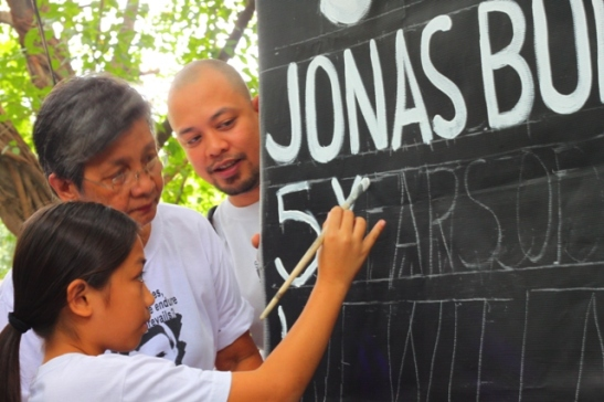 Jonas Burgos' mother, Edita, and other members of the Burgos family painting a sign during the fifth anniversary of his abduction by the AFP (photo courtesy of Bulatlat).