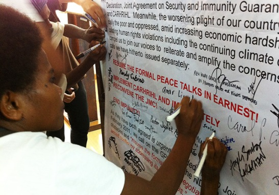 Filipinos, back in March, signing a placard urging the government to resume peace talks with the NDFP (photo by (Ilang-Ilang Quijano/Pinoy Weekly).