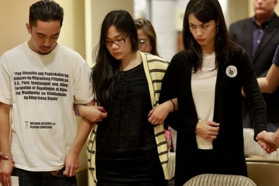 National Alliance for Filipino Concerns officer Ryan Leano (left), Filipino Community Center staff member Darah Macaraeg and Taskforce Haiyan volunteer Josephina Rubio lock arms as they pray (photo by Brant Ward/San Francisco Chronicle).