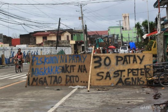 A sign in Tacloban City, Leyte asks authorities to pick the 30 or so dead bodies in one building (photo courtesy of Greenpeace).