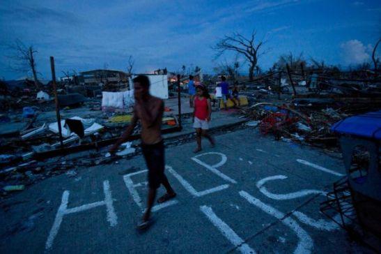 Typhoon Yolanda survivors walking through the wreckage of Tacloban City on November 13th (photo by David Guttenfelder/AP).